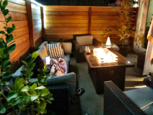 "alt=""picture of a guest enjoying the private patio and fire table at the Luxury Guesthouse in Portland Oregon"""