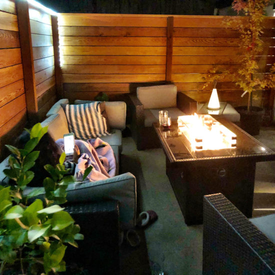 """alt=""""picture of a guest enjoying the private patio and fire table at the Luxury Guesthouse in Portland Oregon"""""""